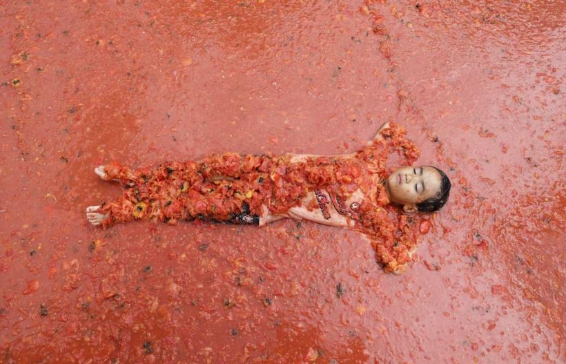 टोमॅटो फेस्टिव्हलदरम्यान टोमॅटोच्या पूलमध्ये निवांत झोपलेला मुलगा. (छाया सौजन्य : रॉयटर्स)