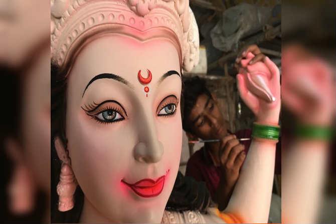 दुर्गादेवीची मुर्ती पूर्ण झाल्यांवर अखेरचा हात फिरवितांना मुर्तिकार ( छायाचित्रकार -प्रदीप दास)